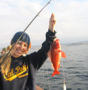 A Cal Poly student holding an orange fish that has been caught to study.