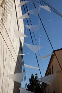 Image of triangular glass pieces hanging from side of building