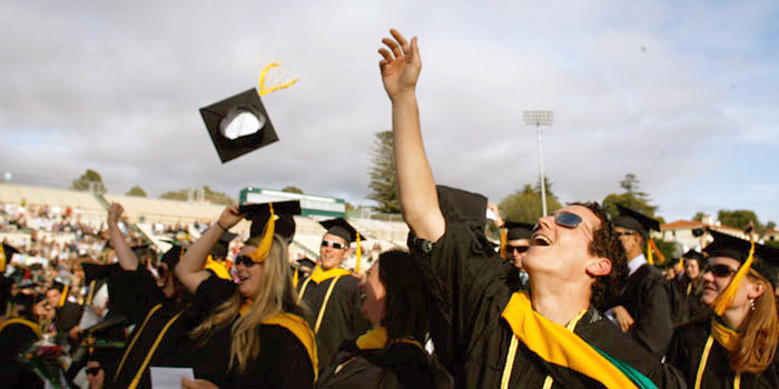 Image of graduates throwing caps in the air after graduation ceremony.