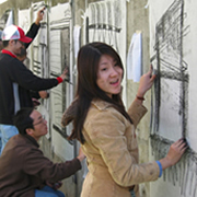 Women student drawing at wall