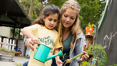 Children tendthe playground's newgarden with Cal Poly  students.