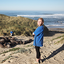 Woman poseses on beach with Elephant seals in the background.