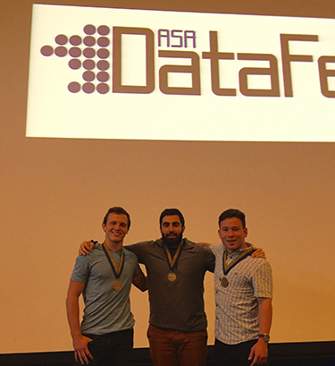 Three men with medals around their necks pose in front of a projector that reads ASA DataDest