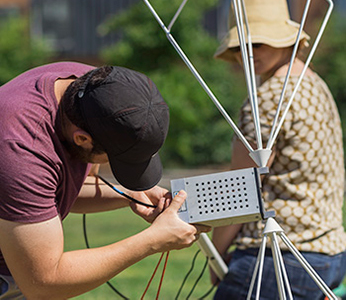 Students assemble a multi-pronged antenna outdoors