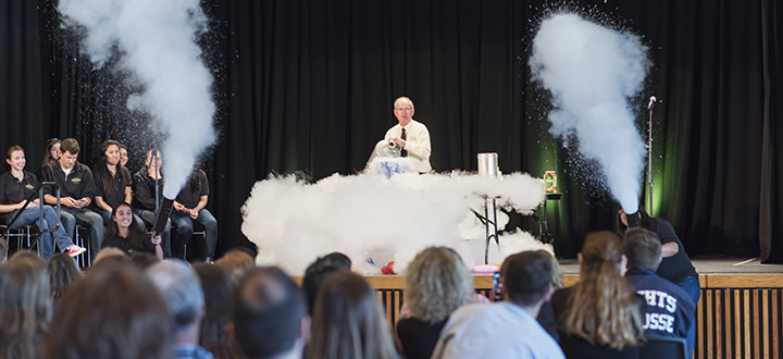 Image of man in behind table performing chemistry demonstration in front of crowd.