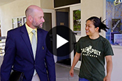 Dean Wendt walking with student with video play button