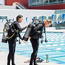Image of student helping another student put on SCUBA gear near pool.