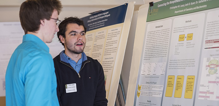 Image of two male students discussing contents of research poster