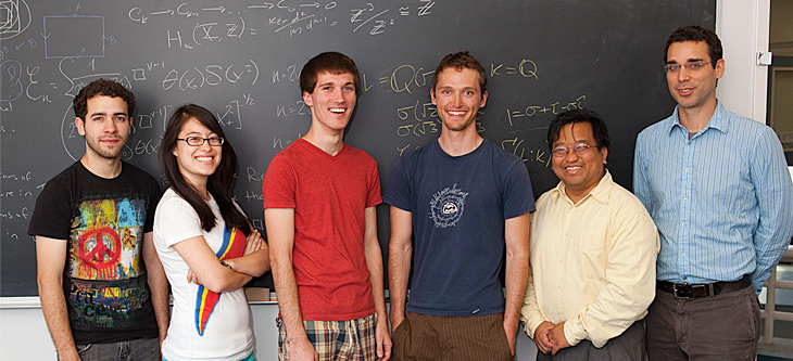 A group of mathematics students and professors in front of a chalkboard.