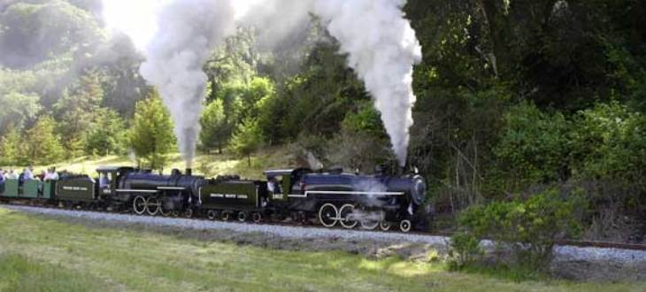 Two 1/3 scale steam locomotives pulling passenger cars