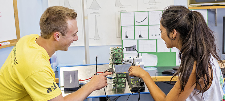 Male student and female student smile while looking at single-board computer