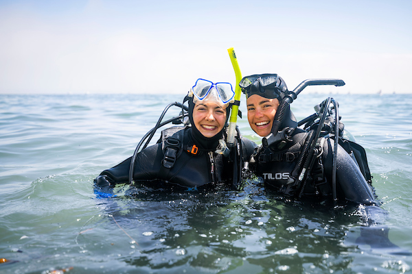two divers chest deep in water smiling