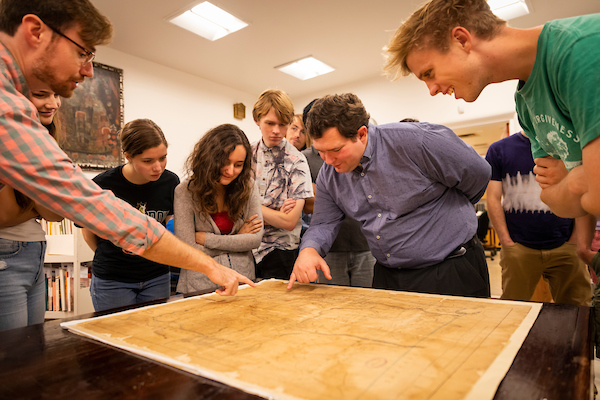 students and professor looking at a map