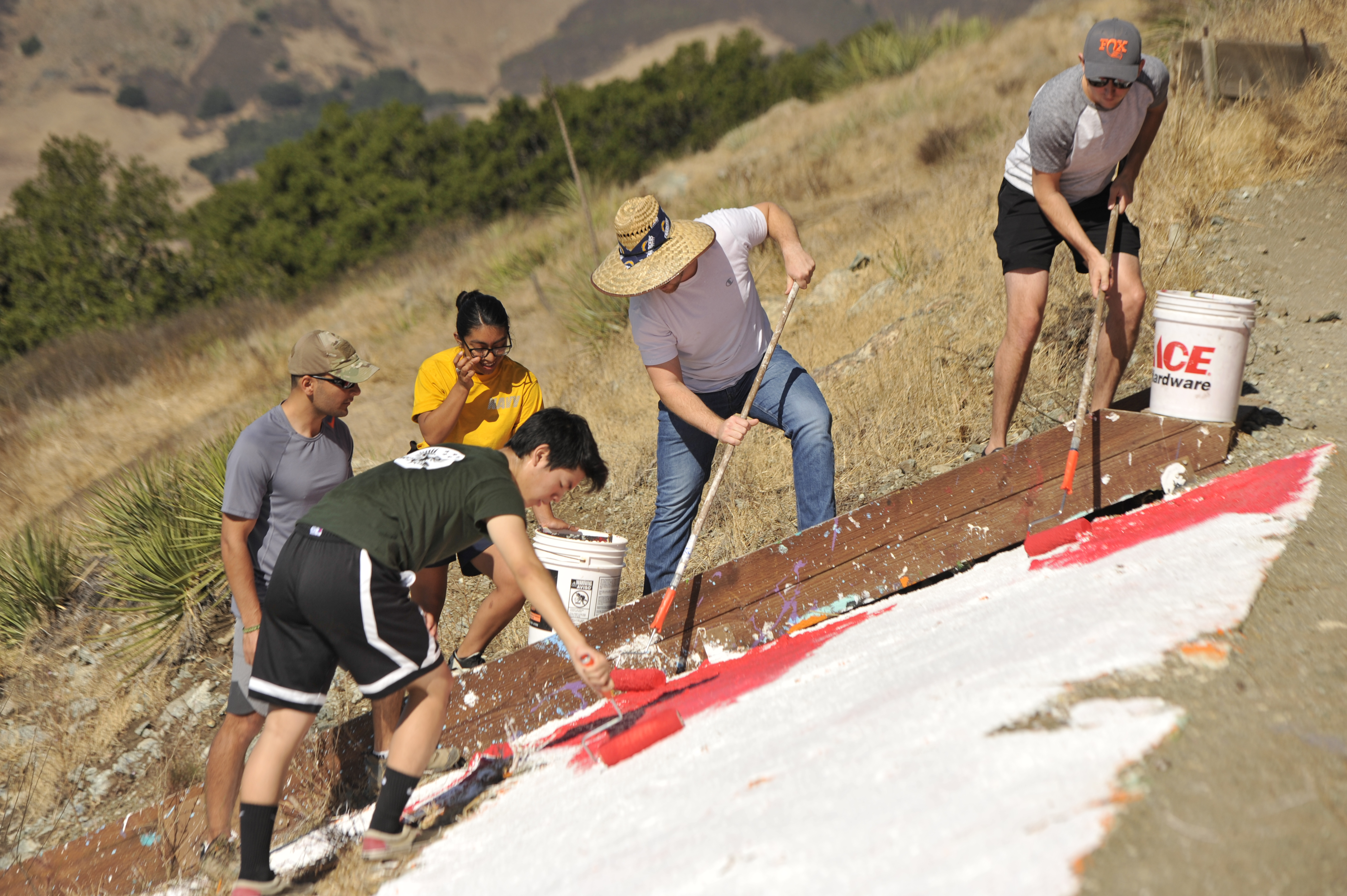 students painting the cal poly P red