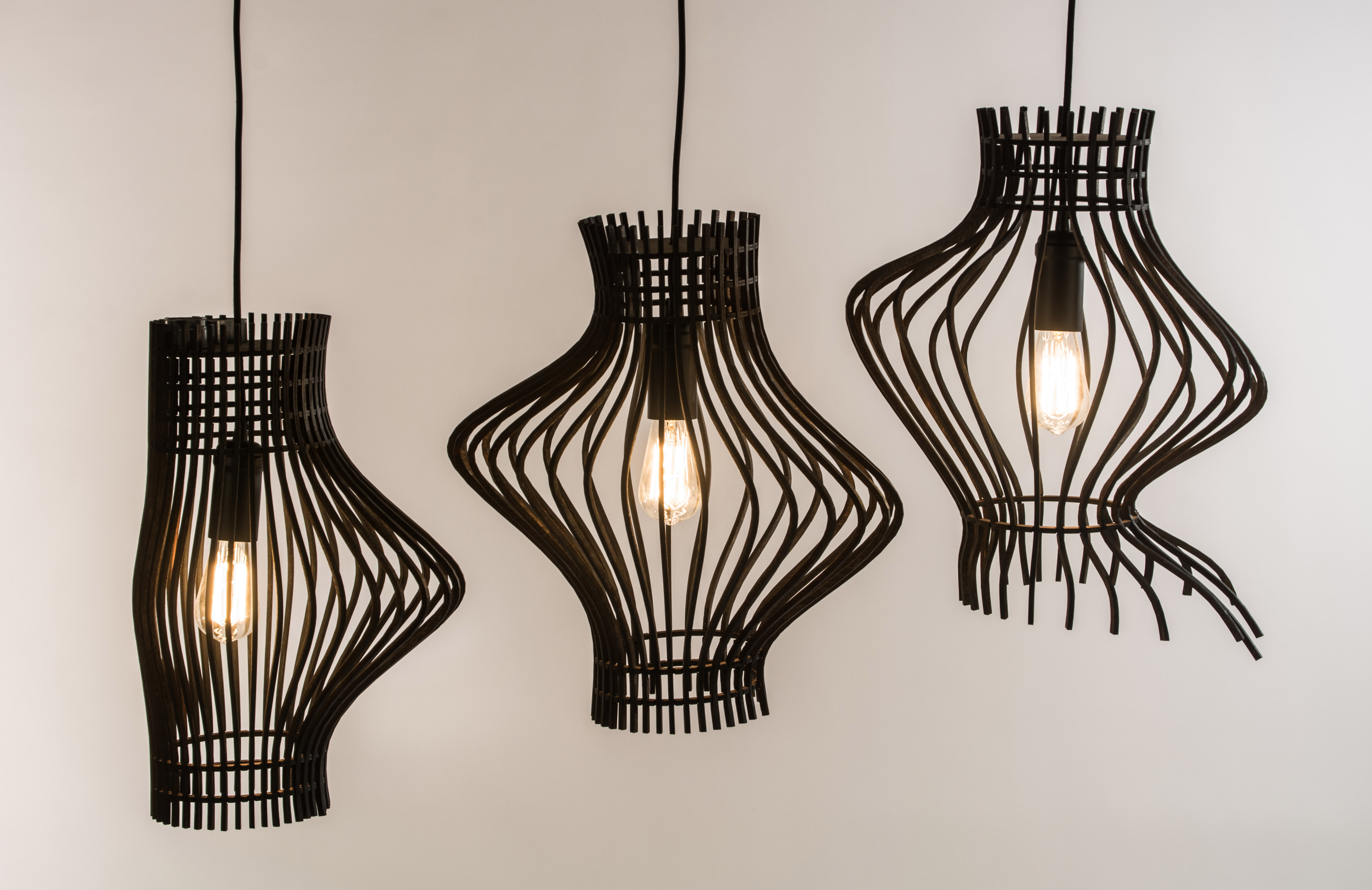 three black metal hanging lamps by Rachel Robinson