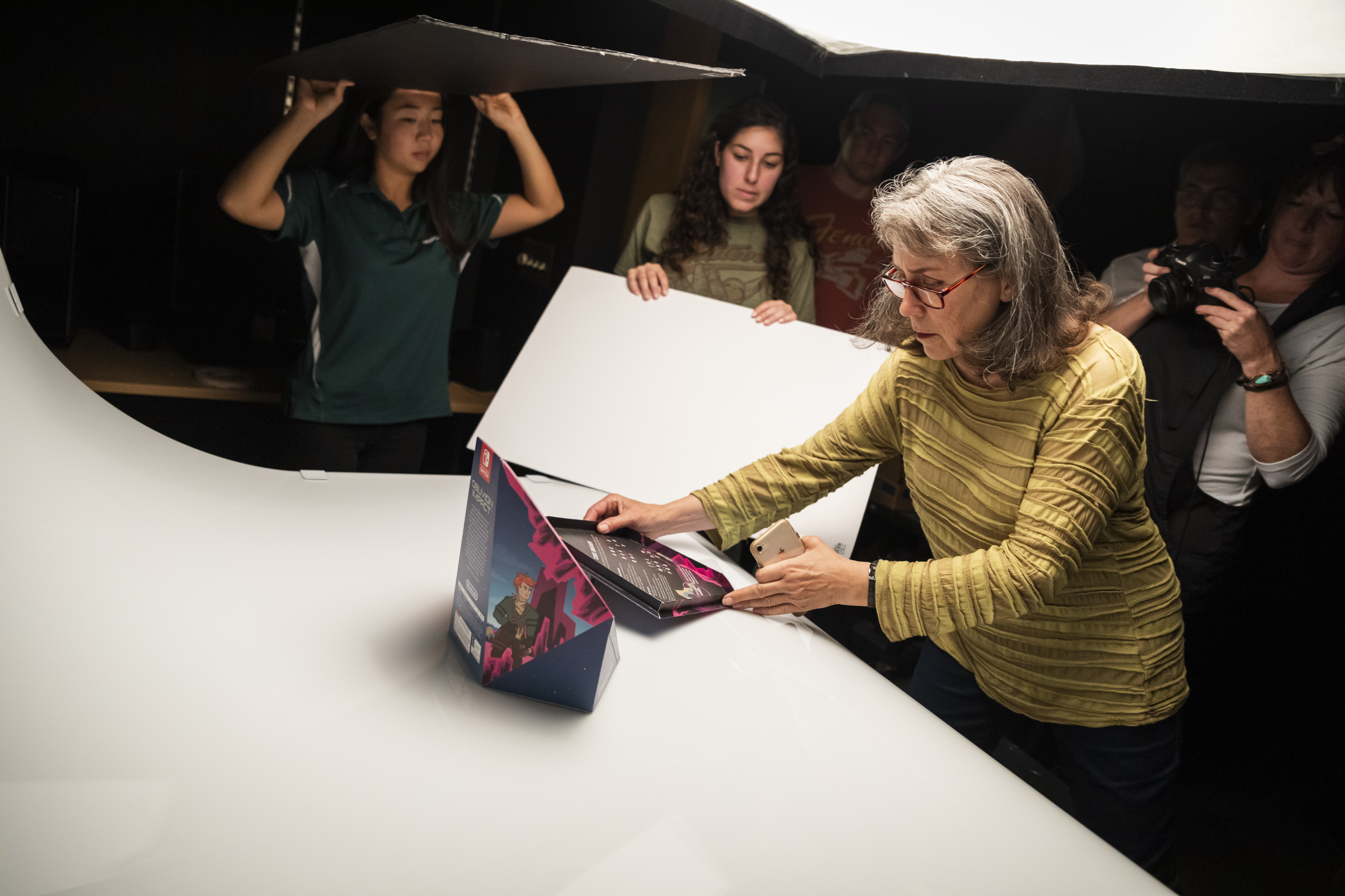 Professor LaPorte works with students to photograph their packaging projects
