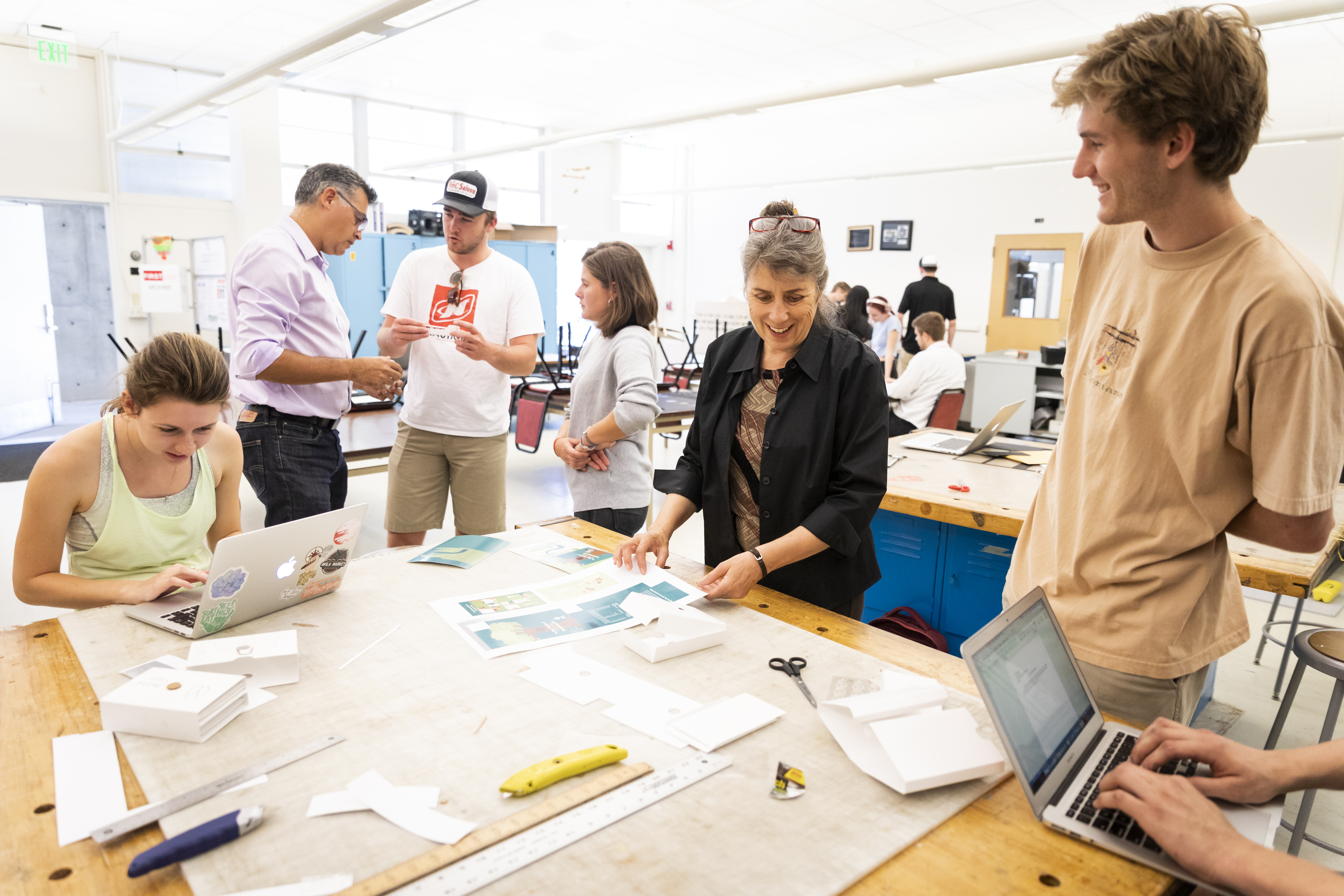 Professors Javier de la Fuente and Mary LaPorte work with packaging design students