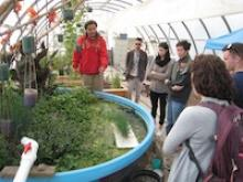 Students gathered in green house listening to lecture