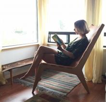 "al Poly fifth-year architecture student Mackenzie Stickney enjoys the comfort of her award-winning entry made of solid stock maple and leather. The lounge chair, titled ""The Montreal,"" received the AIA: Modern Master Award at last year's Vellum Furniture Competition."