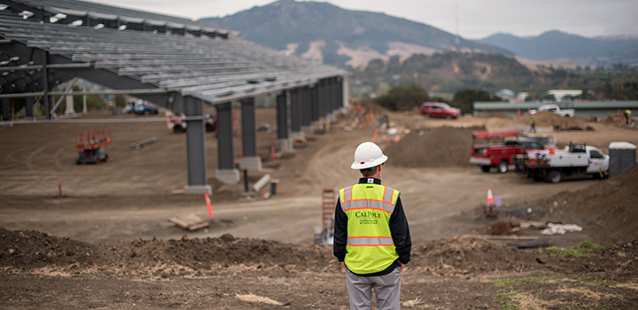 Construction worker overlooking the build site of the Oppenheimer Family Equine Center