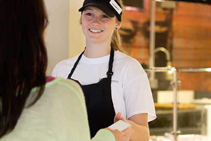 Photo of a campus dining employee smiling as she accepts a credit card from a customer.