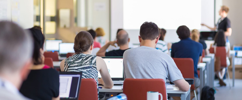 Stock photo of people sitting in a classroom with computers, listening to an instructor.