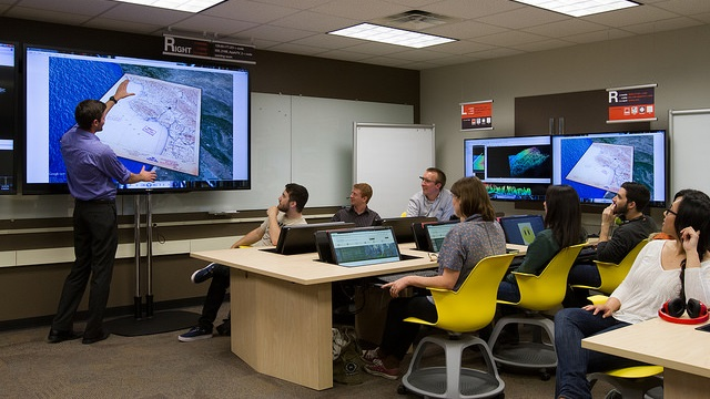 Photo of people in a workshop looking at a map projected onto a screen.