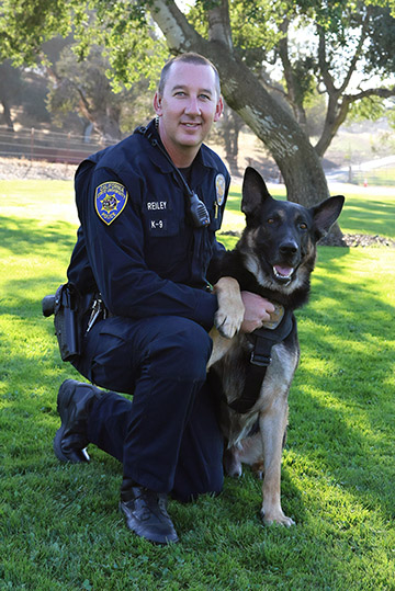 Cal Poly University Police Officer Chad Reiley pictured with K-9 Brisant.