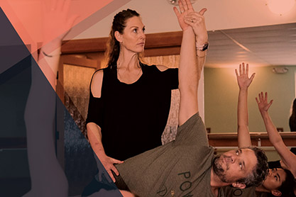 Photo of a female yoga teacher correcting a students' hand in a yoga class.