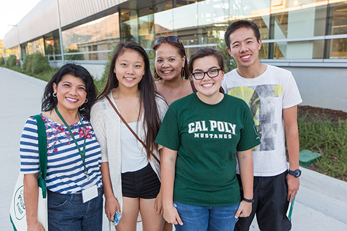 A group of individuals, one wearing a Cal Poly shirt, posing on campus.