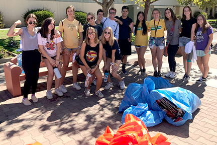 A group of volunteers, including WOW students, pose with some of the material they collected.