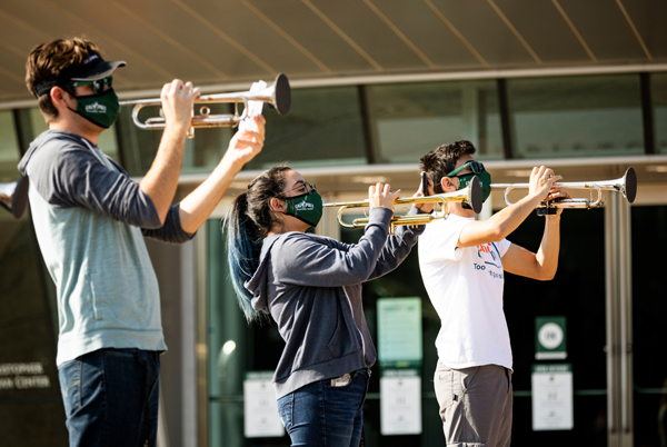 Students in the Mustang Band practice with face coverings outside the Performing Arts Center