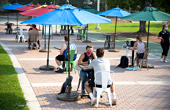 Students sit alone or in pairs with face coverings at tables with brightly colored umbrellas on Mustang Way.