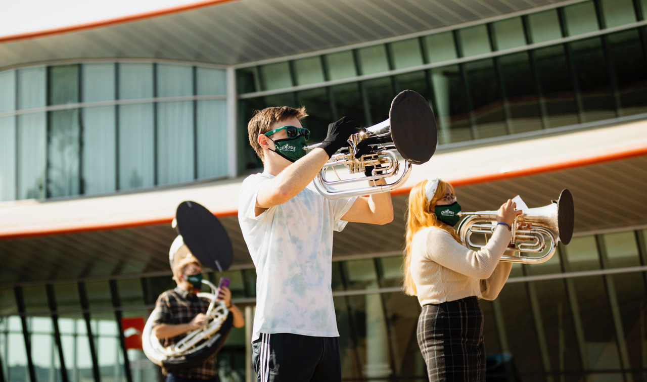 Students in Mustang Band practice with face coverings outside the Performing Arts Center.