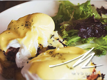 Photo of eggs Benedict and some salad with Myron's logo.