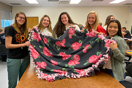 Students in the Cal Poly University Honors Program pose with one of the tie blankets they made this fall.
