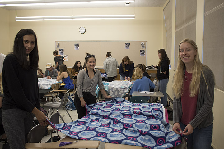 Students in Cal Poly's Honors Program pose for a photo while making tie blankets for the Women's Shelter Program