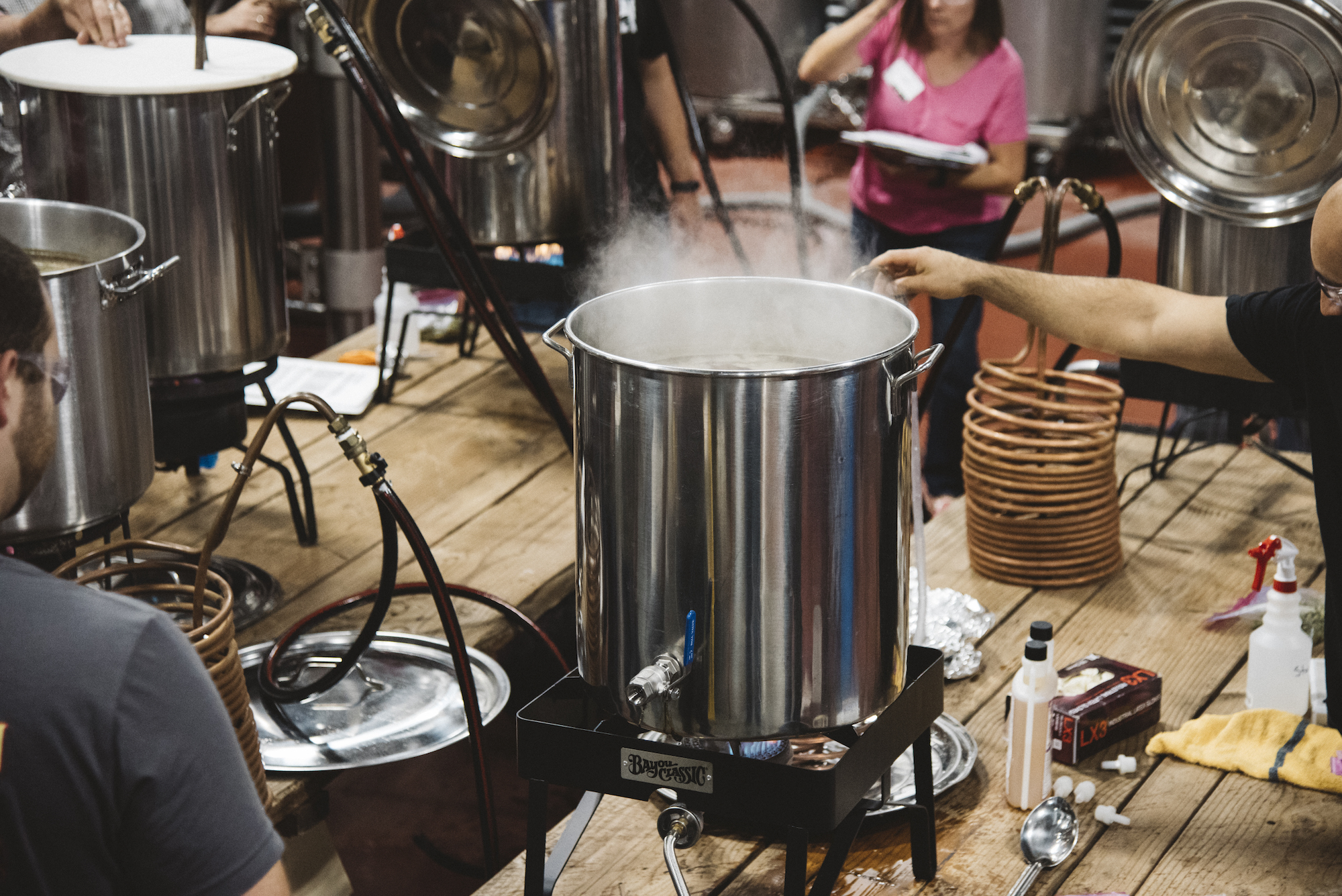 Photo of a home brewing class showing a few large pots in which beer is being brewed.
