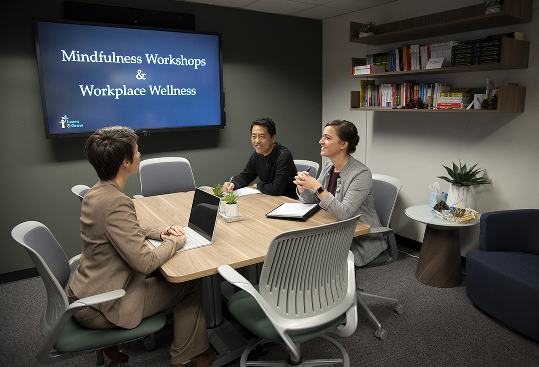 Photo of people sitting around a table with text on a screen reading Mindfulness Workshops and Workplace Wellness.