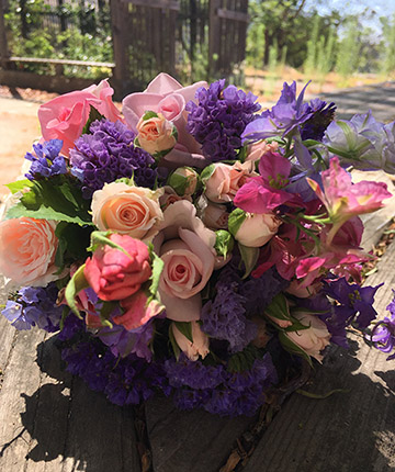 Photo of a large bouquet of pink roses and other types of purple flowers.