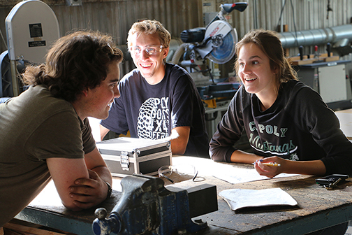 File photo of College of Engineering students seated around a desk, talking and working on a project.