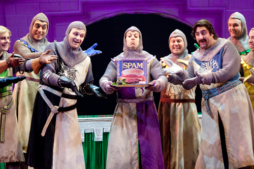 Promotional photo of cast members, including one holding a giant container of Spam, in a production of Spamalot!
