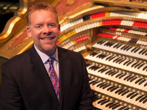 Photo of Christian Elliot and the Forbes Pipe Organ in the background.