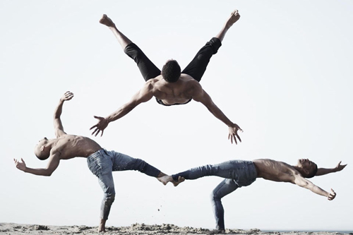 Promotional photo of acrobatics being performed by three individuals.