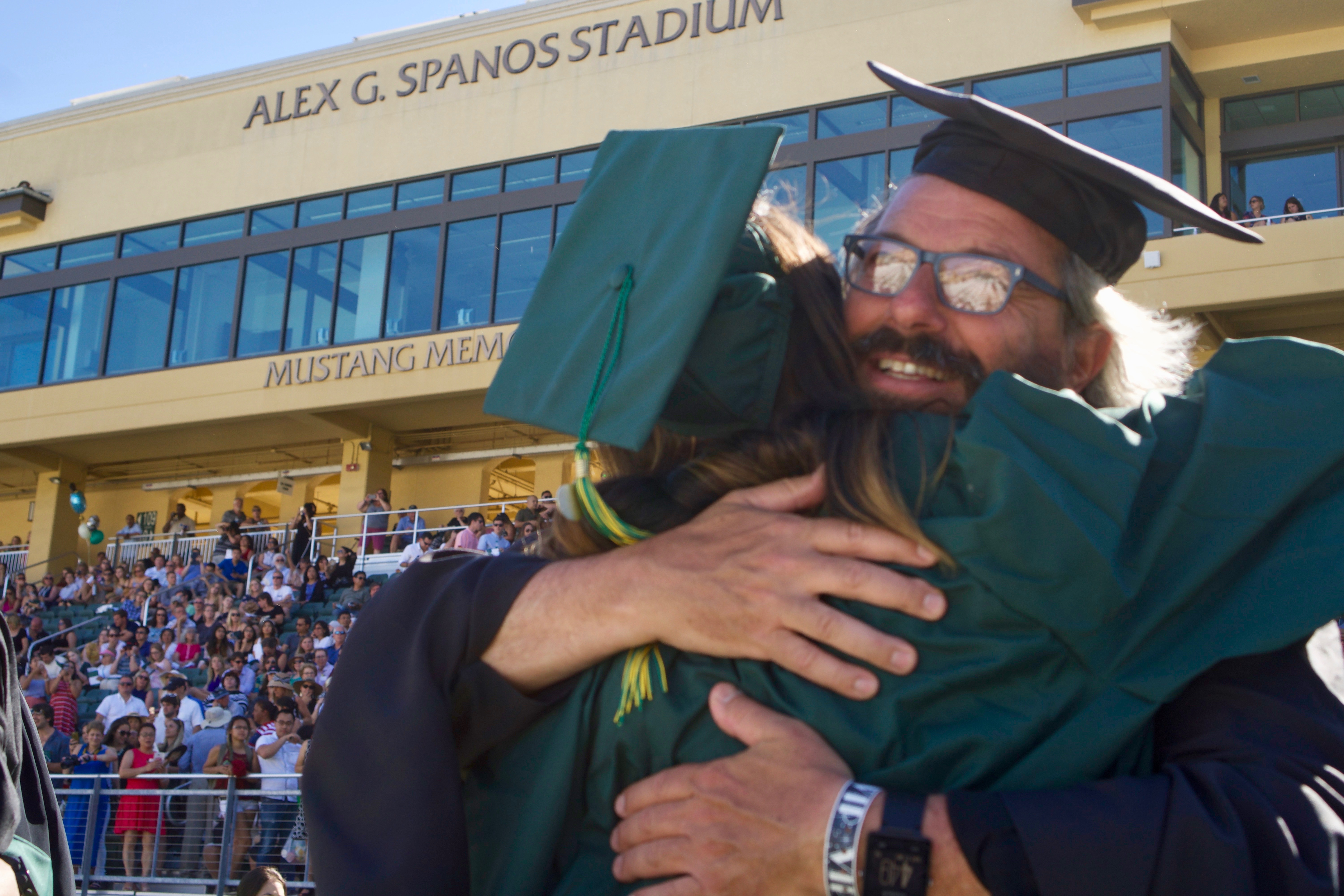 Photo of two people wearing green caps and gowns and hugging in Alex G. Spanos Stadium during a commencement.