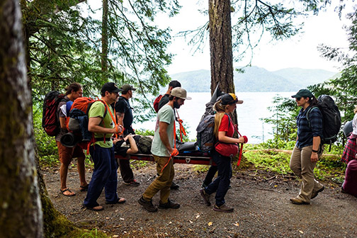 A group of people hiking and carrying a stretcher. Photo by Kyle Wilson.