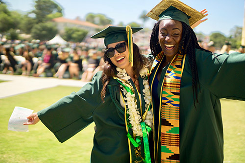 Photo of two women in green caps and gowns with arms around each other posing during a graduation ceremony