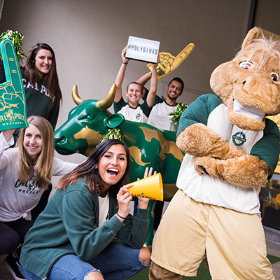 Photo of five Cal Poly students with Musty the Mustang, one student holding sign reading Poly Gives and the others with Cal Poly themed foam fingers and a bullhorn