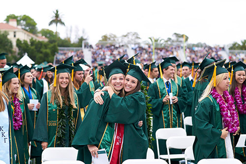 Photo of two female students hugging at a previous commencement ceremony, surrounded by other graduating students.