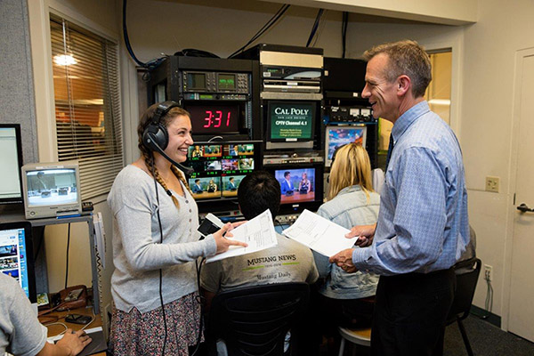 Photo of a student a professor smiling during a broadcast at CPTV at Cal Poly.